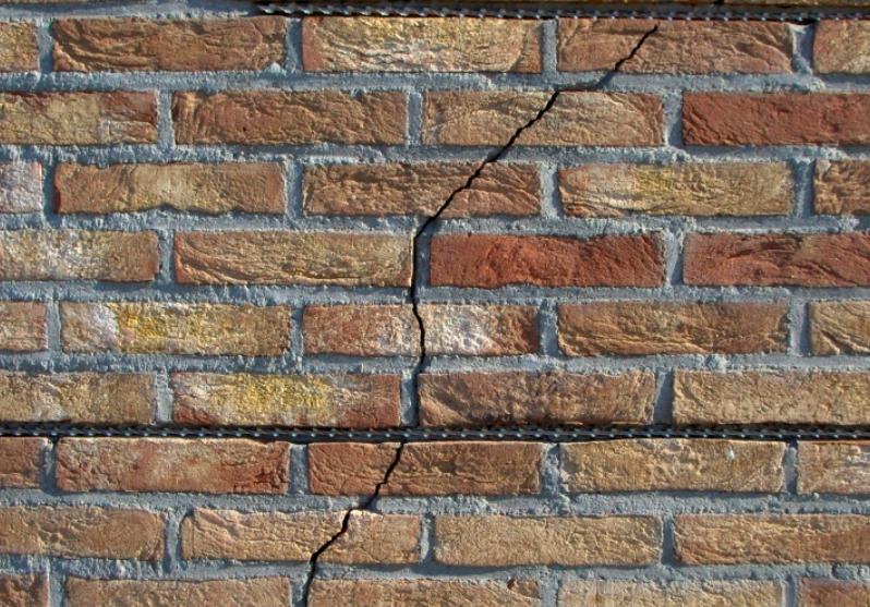 Bruine muur met een scheur in het midden